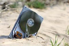 Потерянный компьютер hardrive в песке Стоковые Изображения