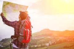 Потерянный hiker с рюкзаком проверяет карту для того чтобы найти направления стоковое фото rf