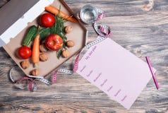 Потеря веса и здоровая концепция еды Открытая коробка пиццы с сырцовыми овощами в ей, стеклом воды, измеряя лентой и планом диеты стоковые фотографии rf