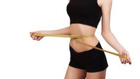 Потеря веса, тонкое тело, здоровая концепция образа жизни Девушка фитнеса измеряя ее талию с лентой измерения, изолированной на б стоковые изображения rf