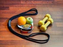 Потеря веса через тренировку и правильную диету гантели, детандер, плодоовощи, сантиметр стоковая фотография