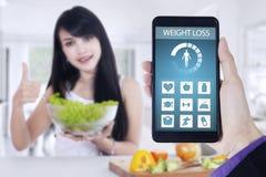 Потеря веса app и женщина держат салат стоковая фотография