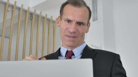 Потеря, разочарованный средний достигший возраста бизнесмен работая на ноутбуке