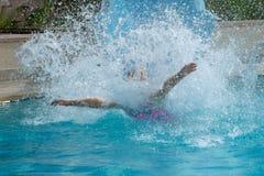 Потеха водных горок в бассейне летом разбивая в воду делая большой выплеск стоковые фотографии rf