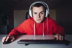 Потеха в gamer вечера молодом играет видеоигры на компьютере стоковые изображения