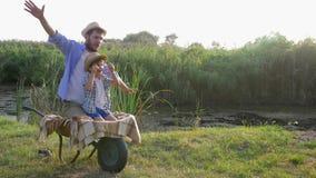 Потеха для семьи, отец и сын представляют что они летает как самолет сидя совместно в тачке на сельском акции видеоматериалы