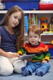 Потеха девушки и брата используя цифровое comput таблетки Стоковое Изображение RF