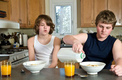 Потеха завтрака семьи - предназначенные для подростков братья имея хлопья: беспристрастные съемки стоковое фото rf
