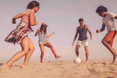 потеха имея как раз Группа в составе жизнерадостное молодые люди играя с soc Стоковое Фото