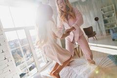потеха имея совместно Милая маленькая девочка скача на кровать с ним Стоковое Фото