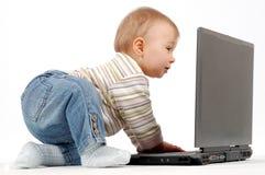 потеха младенца имея компьтер-книжку Стоковые Фото