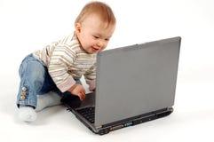 потеха младенца имея компьтер-книжку Стоковые Изображения