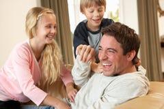 потеха отца детей имея детенышей софы стоковое фото rf