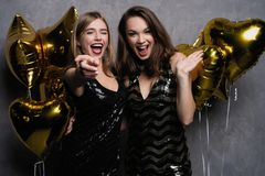 Потеха партии красивейшие празднуя девушки изолировали новую над белым годом Портрет шикарных усмехаясь молодых женщин наслаждаяс стоковое фото
