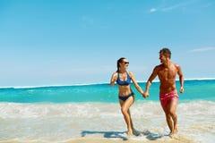 Потеха пар на пляже Романтичные люди в влюбленности бежать на море стоковая фотография rf