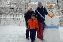 Потеха семьи внешняя и снеговик здания Стоковые Изображения RF