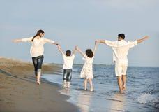 потеха семьи пляжа счастливая имеет детенышей захода солнца Стоковое фото RF