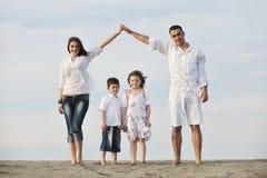 потеха семьи пляжа счастливая имеет детенышей Стоковая Фотография