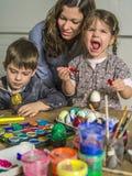 Потеха семьи украшая пасхальные яйца Стоковые Фото
