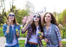 Потеха счастливых девочка-подростков hawing тратит время совместно в парке города Стоковая Фотография RF