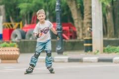 Потеха счастливого мальчика faving на scates ролика на естественном backgroun Стоковое Фото