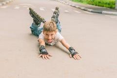 Потеха счастливого мальчика faving на scates ролика на естественном backgroun Стоковая Фотография