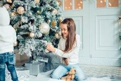 Потеха havung 2 маленьких девочек перед рождественской елкой Стоковое Изображение