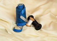 3 потока других цветов и голубой переплетенной рулетки на бежевой ткани стоковая фотография