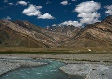Поток бирюзы реки пропускает через высокие горы долины: на заднем плане триангулярные гребни холмов  Стоковое фото RF
