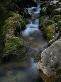 Поток воды который идет среди больших камней Стоковые Изображения
