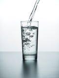 Поток воды льет в стекло стоковая фотография rf