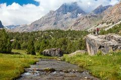 Поток горы и женские Hikers на утесе Стоковое фото RF