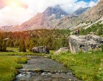Поток горы и женские Hikers на утесе Стоковое Фото