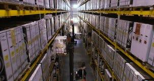 Поток операций в складе фабрики, работники сделает работу в современном складе Летание между строками в запасе сток-видео