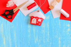 Поток орнамента, ножниц, красных и белых дома рождественской елки войлока, войлок соединяет, заполнитель на голубой деревянной пр Стоковая Фотография