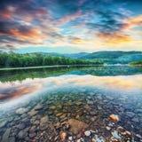Поток реки горы воды в утесах с величественным заходом солнца стоковое изображение rf