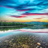 Поток реки горы воды в утесах с величественным заходом солнца стоковые изображения