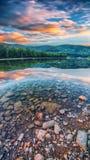 Поток реки горы воды в утесах с величественным заходом солнца стоковое фото rf
