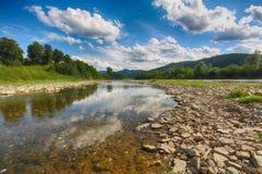 Поток реки горы воды в утесах с голубым небом стоковое фото