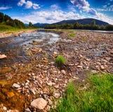 Поток реки горы воды в утесах с голубым небом стоковые изображения rf