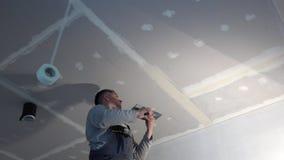 Потолок гипсокартона гипса человека квалифицированного рабочего spackling с лопаткой сток-видео