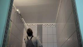 Потолок bathroom краски работника с инструментом ролика сток-видео
