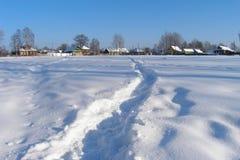 Потоптанный путь в снеге к деревне, Россия Стоковые Фото