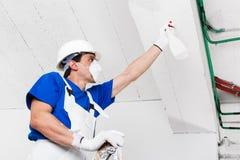 Потолок работника распыляя с бутылкой брызга Стоковое Фото