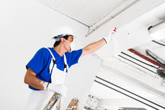 Потолок работника распыляя с бутылкой брызга Стоковые Изображения