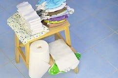 Потребности для младенцев: пеленки ткани, вкладыши ворсистого, изменяя пусковая площадка подготовлены на деревянной табуретке Стоковая Фотография