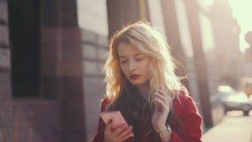 Потревоженная бизнес-леди в красном пальто идет около бизнес-центра в городе, используя мобильный телефон app Устоичивая съемка к акции видеоматериалы