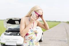 Потревоженная женщина используя мобильный телефон на проселочной дороге с сломанный вниз с автомобиля в предпосылке Стоковое Изображение