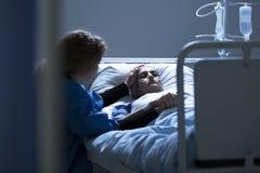 Потревоженная женщина попечителя поддерживая умирая Стоковые Изображения