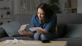 Потревоженная женщина проверяя получения банка в ночи видеоматериал